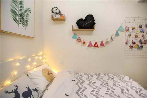 抽屉式床头柜和墙壁置物架都是为了增加收纳空间,台灯和星星串灯则是让房间变得温馨的利器。方格网片和小彩旗的装饰效果杠杠的。